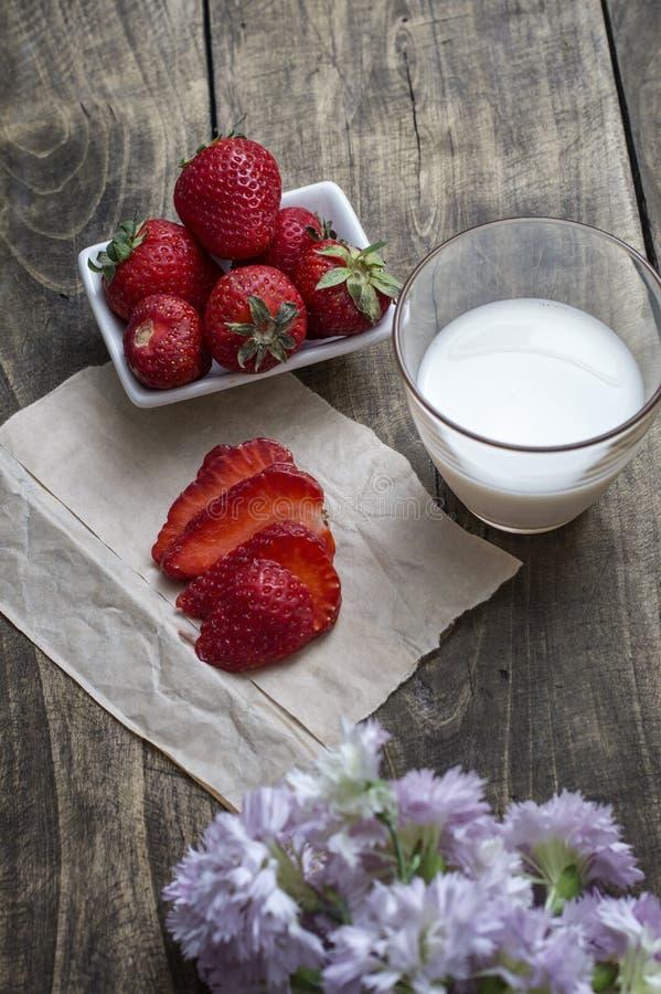 Verse rijpe aardbei in kom en melk over houten lijstbackgro stock foto's