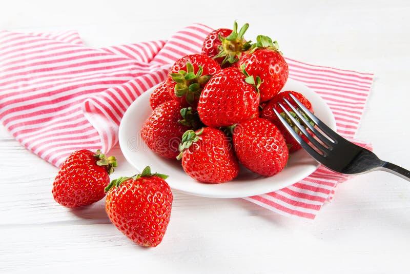 Verse rijpe aardbeien op een plaat Witte houten lijst, servet in rode en witte strepen stock afbeeldingen