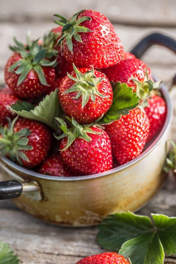 Verse rijpe aardbeien in uitstekende keukenpot op oude tuinlijst stock foto's