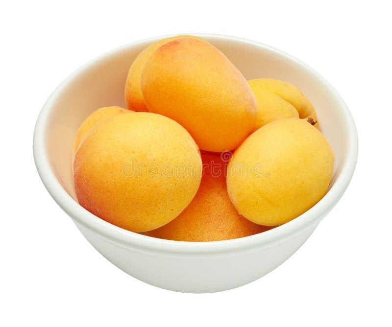 Verse rijpe abrikoos in ceramische die kom op witte achtergrond wordt geïsoleerd Ingrediënten voor het koken Hoogste mening royalty-vrije stock foto's