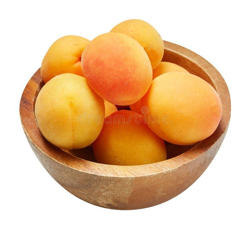 Verse rijpe abrikoos in houten die kom op witte achtergrond wordt geïsoleerd Ingrediënten voor het koken Hoogste mening royalty-vrije stock afbeelding