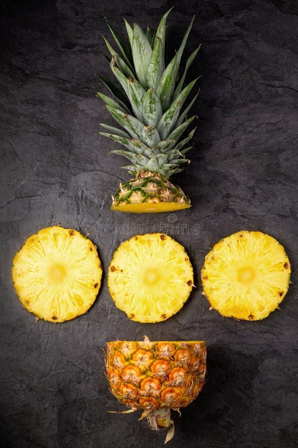 Verse rijpe ananasdwarsdoorsneden op donkere verticale achtergrond, royalty-vrije stock afbeeldingen