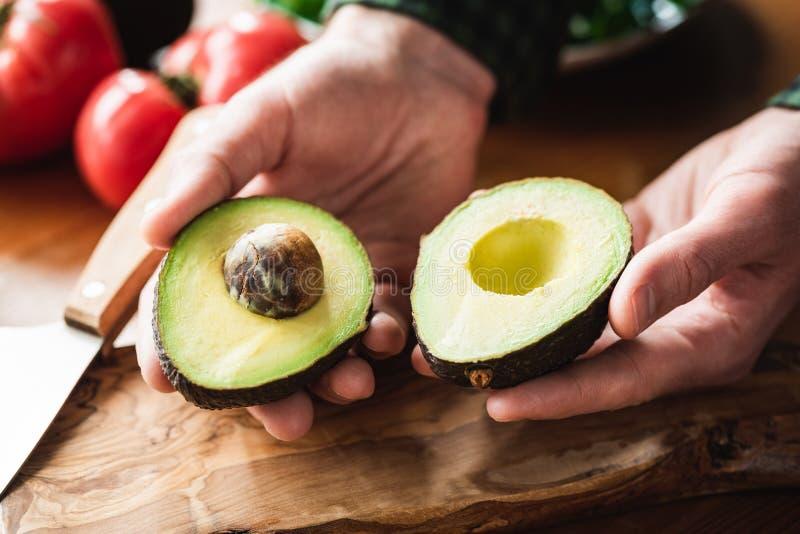 Verse rijpe avocado in mannelijke handen stock afbeelding