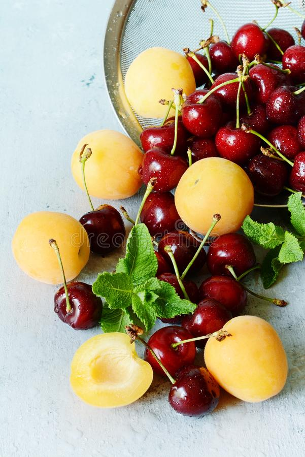 Verse rijpe de zomerbessen en vruchten perziken, abrikozen, kers in een vergiet Zoete vruchten met exemplaarruimte voor tekst royalty-vrije stock afbeelding