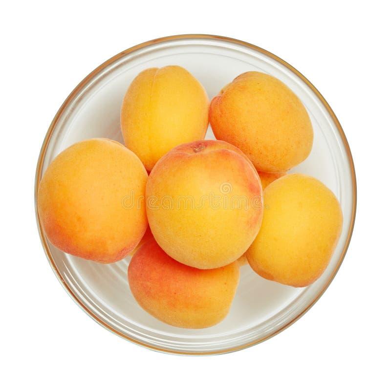 Verse rijpe die abrikoos in glaskom op witte achtergrond wordt geïsoleerd Ingrediënten voor het koken Hoogste mening stock afbeeldingen