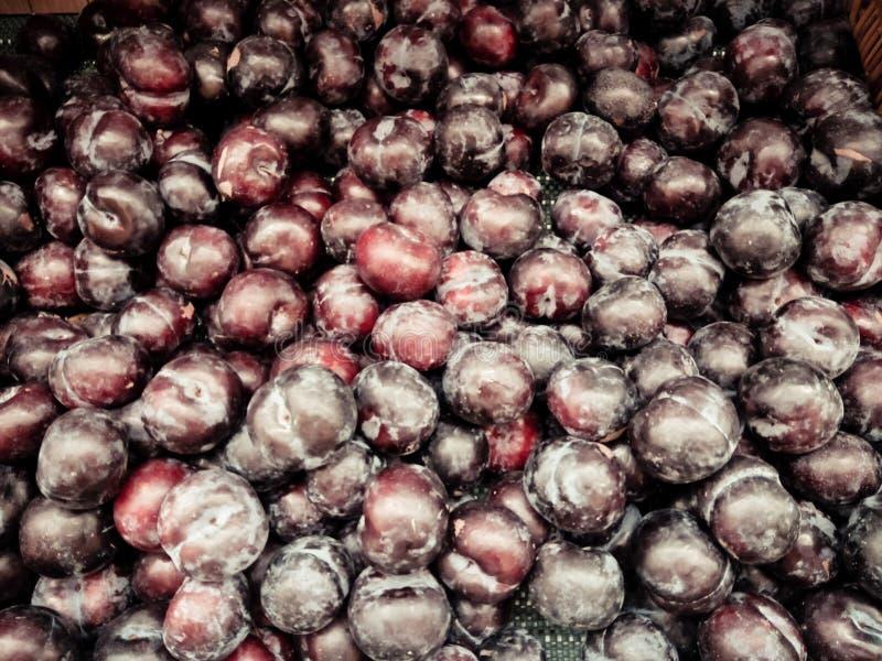 Verse rijpe die pruimen op lijst in markt worden geplaatst Organisch rood pruimenfruit in stapel bij lo royalty-vrije stock fotografie