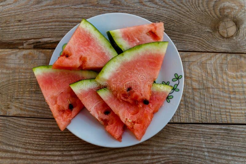 Verse rijpe gesneden watermeloen in witte plaat op rustieke houten lijst stock afbeelding