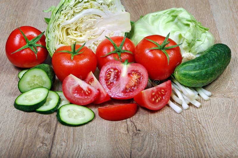 Verse rijpe groenten - tomaten, kool, groene uien en komkommer stock afbeeldingen