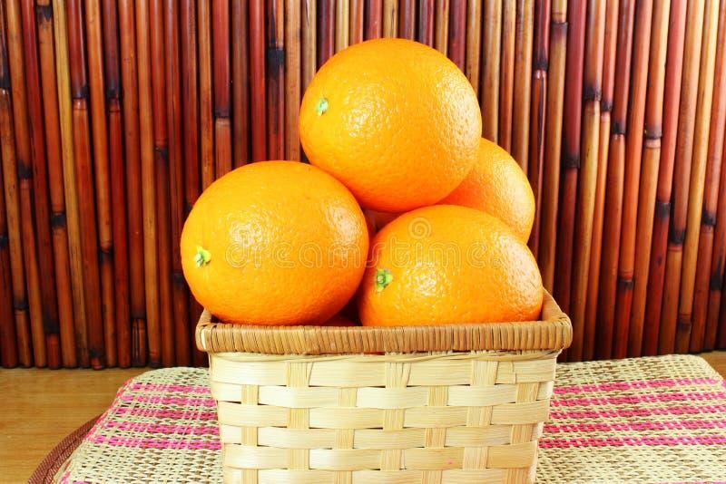 Verse rijpe oranje vruchten in bamboemand op bamboeachtergrond stock afbeelding