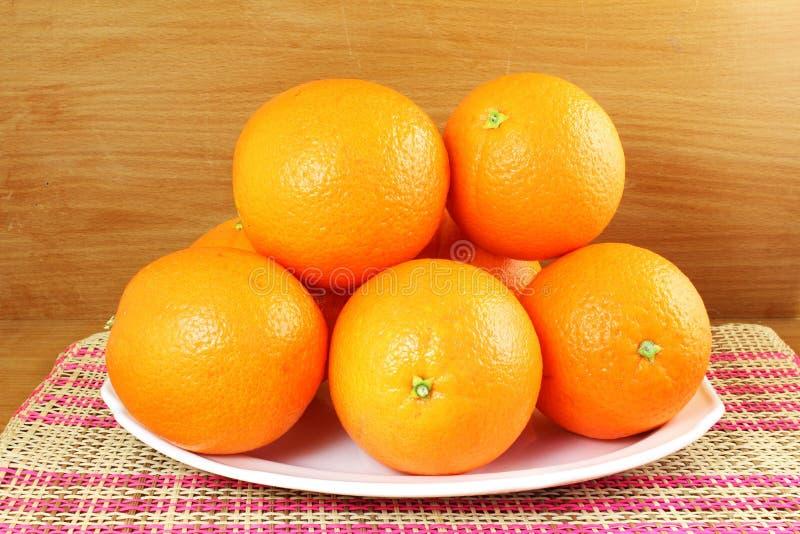 Verse rijpe oranje vruchten in plaat op houten achtergrond royalty-vrije stock foto
