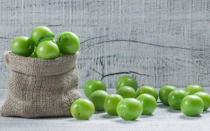 Verse rijpe organische groene pruimen of reine-claude in jutezak op houten achtergrond stock foto