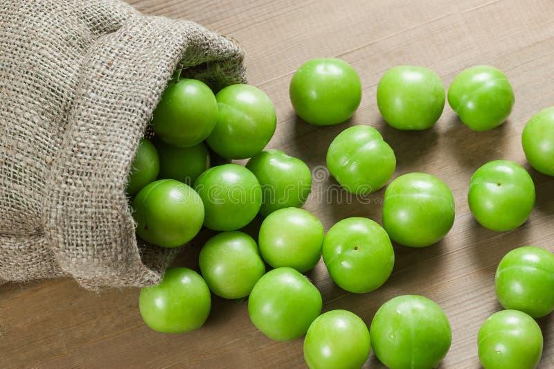 Verse rijpe organische groene pruimen of reine-claude in jutezak op houten achtergrond stock afbeeldingen