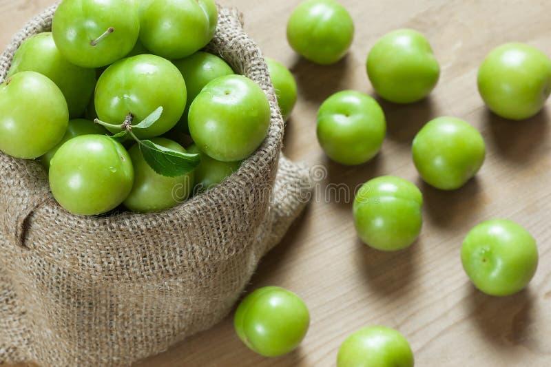 Verse rijpe organische groene pruimen of reine-claude in jutezak op houten achtergrond stock foto's