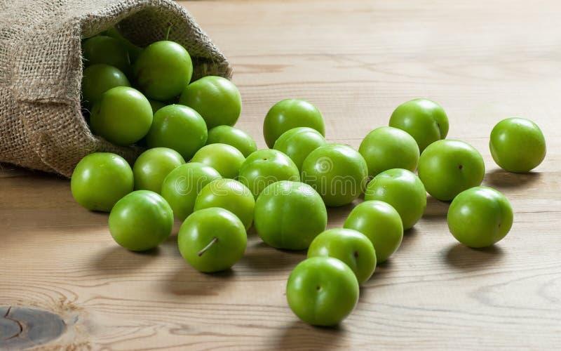 Verse rijpe organische groene pruimen of reine-claude in jutezak op houten achtergrond royalty-vrije stock afbeeldingen