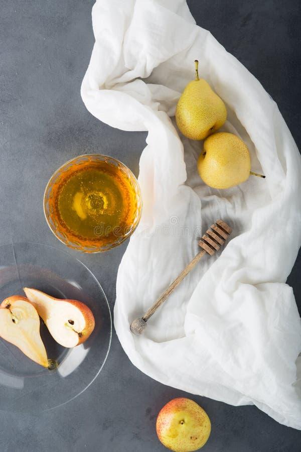 Verse rijpe peren en geurige zoete honing op de lijst stock afbeelding