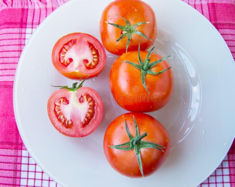 Verse rijpe rijpe rode tomaten en besnoeiingstomaat met waterdalingen en groene peduncle op witte plaat - hoogste mening, organis royalty-vrije stock fotografie