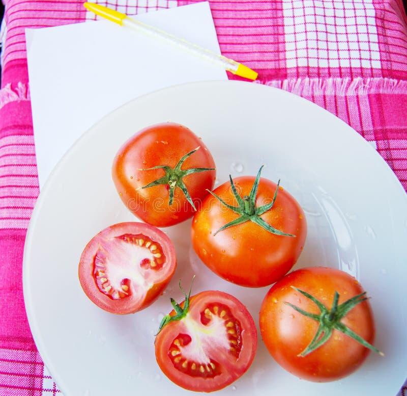 Verse rijpe rode tomaten en gesneden tomaten met waterdalingen en groene peduncle op een witte plaat, naast een blad van Blocnote stock afbeelding