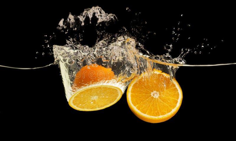 Verse rijpe sinaasappelen die in water met plons bespatten royalty-vrije stock foto's