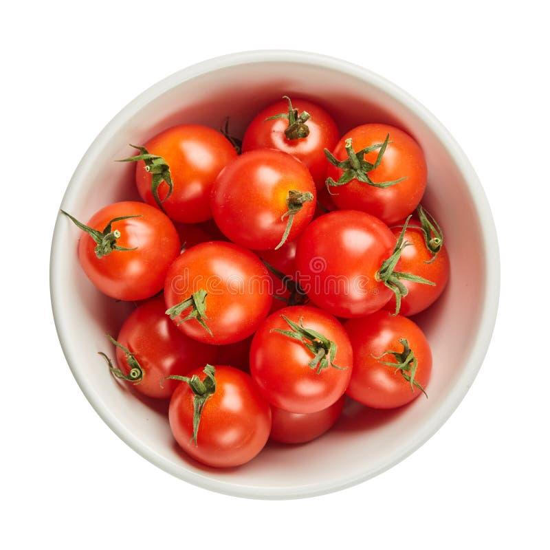 Verse rijpe tomaten in ceramische die kom op witte achtergrond met groen blad wordt geïsoleerd Ingrediënten voor het koken Hoogst stock foto's