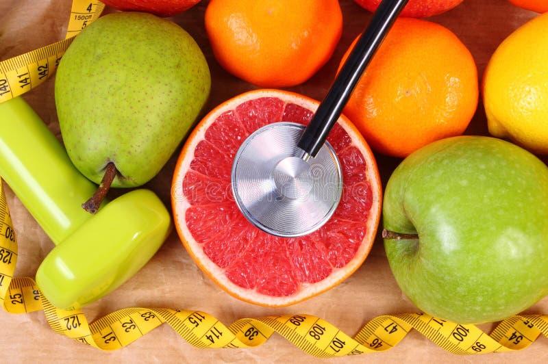Verse rijpe vruchten, meetlint, stethoscoop en domoren voor geschiktheid, gezond levensstijlenconcept stock afbeelding