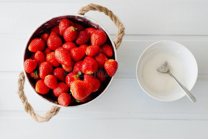 Verse rode aardbeien in witte kom en sugarbowl stock fotografie