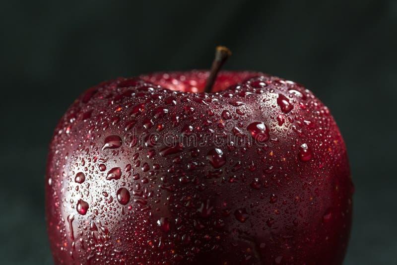 Verse rode appel met druppeltjes van water tegen zwarte achtergrond stock foto