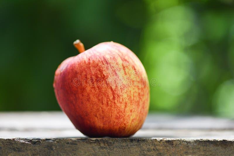Verse rode appel op houten lijst en aard groene achtergrond royalty-vrije stock foto