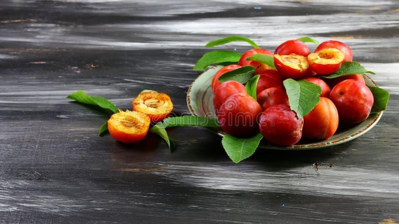 Verse rode pruimen met bladeren op een ceramische plaat Op een donkere achtergrond Vrije ruimte voor tekst Vlak leg royalty-vrije stock fotografie