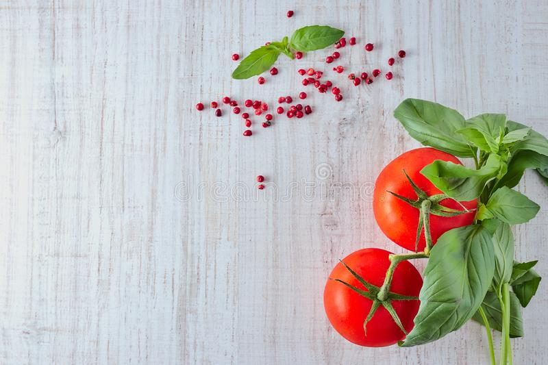 Verse rode tomaten met een bos van Basilicum op een houten lijst De ruimte van het exemplaar De mening vanaf de bovenkant Natuurl royalty-vrije stock foto's