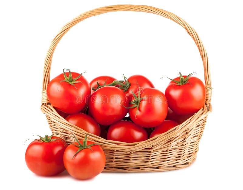 Verse rode tomaten in rieten mand stock afbeeldingen