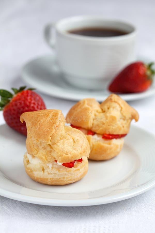 Verse roomrookwolk met slagroom en aardbeien op witte pl stock foto's