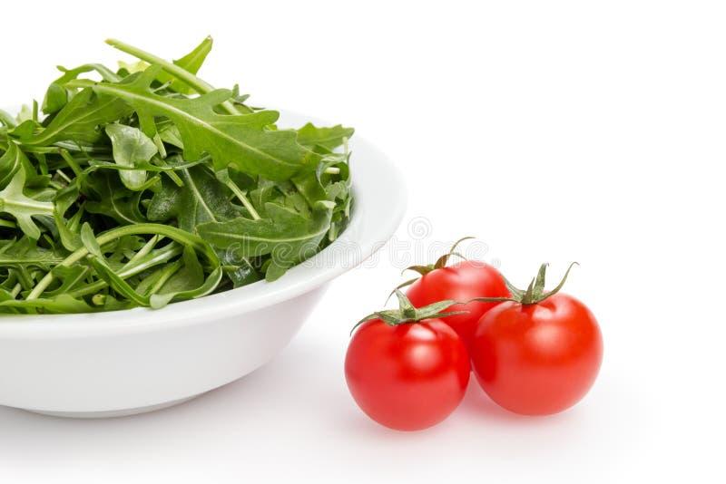 Verse rucolabladeren in een kom en tomaten royalty-vrije stock afbeelding
