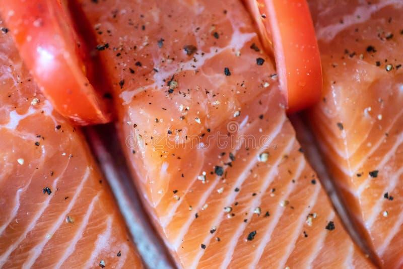 Verse ruwe de zalmfilets van de close-upmening met kruiden en kruiden op bakseldienblad klaar om in oven worden gekookt stock afbeelding
