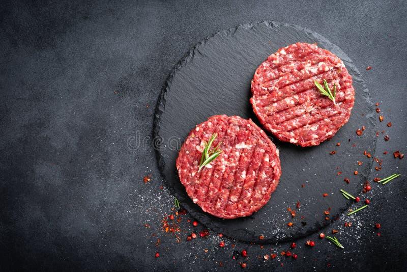 Verse ruwe fijngehakte burgers van het rundvleeslapje vlees met kruiden royalty-vrije stock fotografie