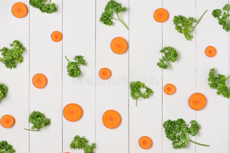 Verse ruwe gepelde wortelplakken met groenten op houten lijst stock foto