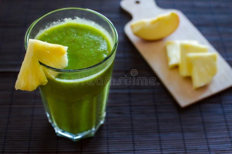 Verse ruwe groene spinazie smoothie met ananas, appel en zaden stock fotografie
