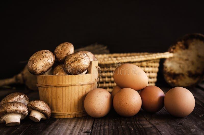 Verse ruwe koninklijke champignons en eieren op donkere houten rustieke lijst royalty-vrije stock foto's