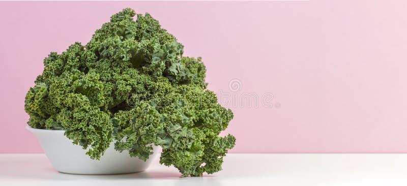 Verse ruwe organische groene boerenkoolbladeren van boerenkool op witte plaat met roze achtergrond royalty-vrije stock afbeeldingen