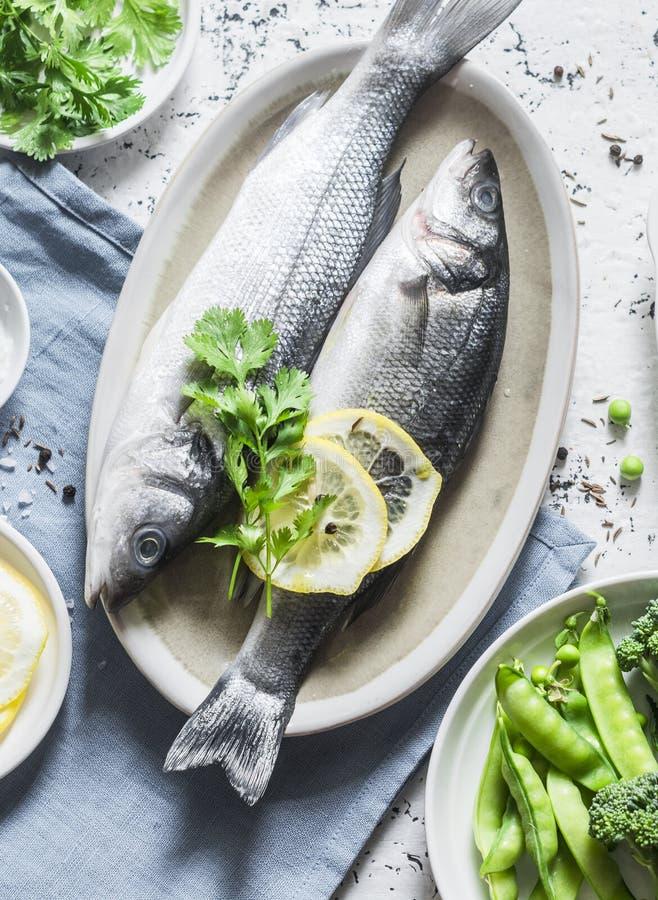 Verse ruwe overzeese baarzen en groenten op een lichte achtergrond, hoogste mening Gezond voedsel royalty-vrije stock foto