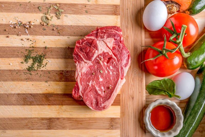 Verse ruwe rundvleeslapje vlees en eieren en groente stock fotografie