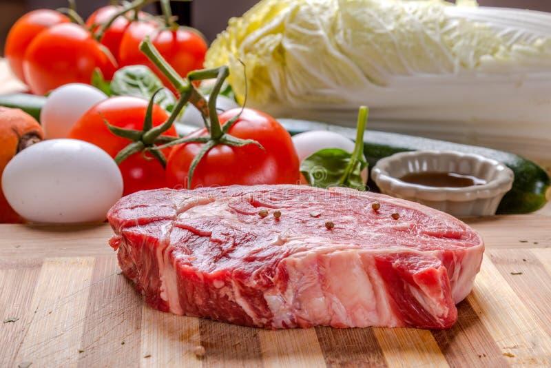 Verse ruwe rundvleeslapje vlees en eieren en groente royalty-vrije stock afbeelding