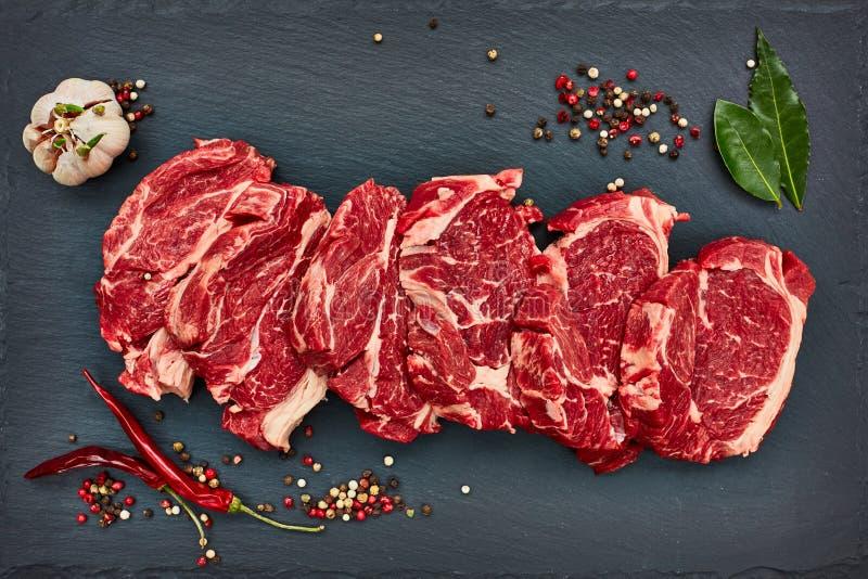 Verse ruwe rundvleeslapjes vlees met koele peper op zwarte leiraad De ruimte van het exemplaar royalty-vrije stock foto's