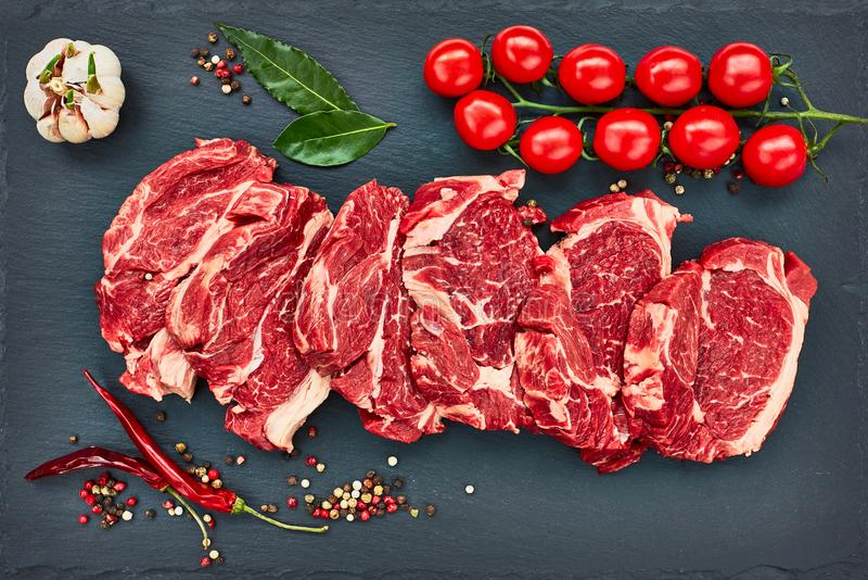 Verse ruwe rundvleeslapjes vlees met peper en tomaten op zwarte leiraad royalty-vrije stock foto