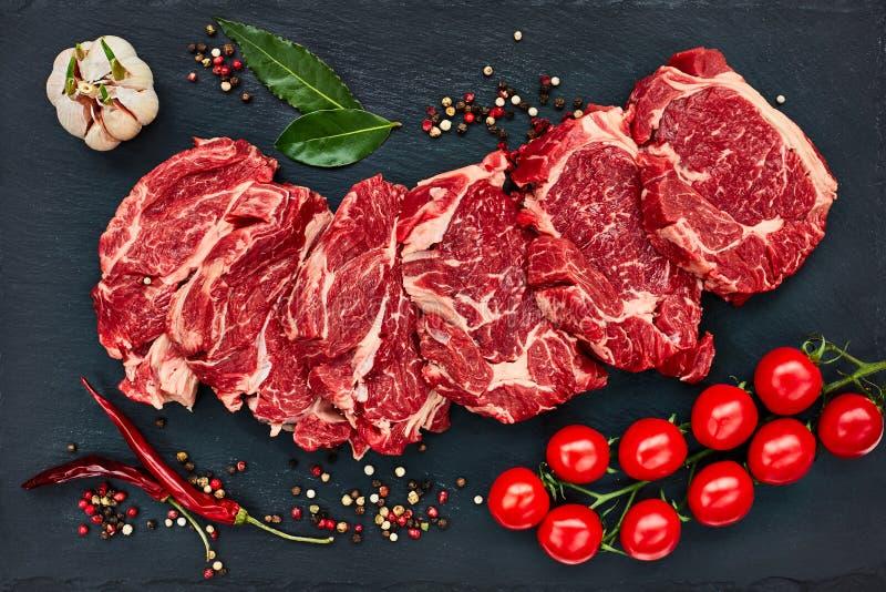 Verse ruwe rundvleeslapjes vlees met peper en tomaten op zwarte leiraad De ruimte van het exemplaar royalty-vrije stock afbeelding