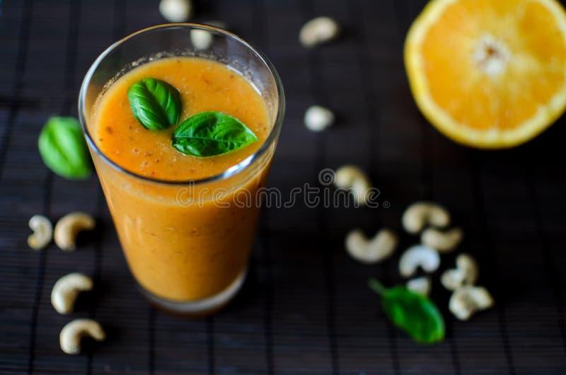 Verse ruwe sinaasappel smoothie met appel, wortel en noten op de donkere achtergrond royalty-vrije stock fotografie