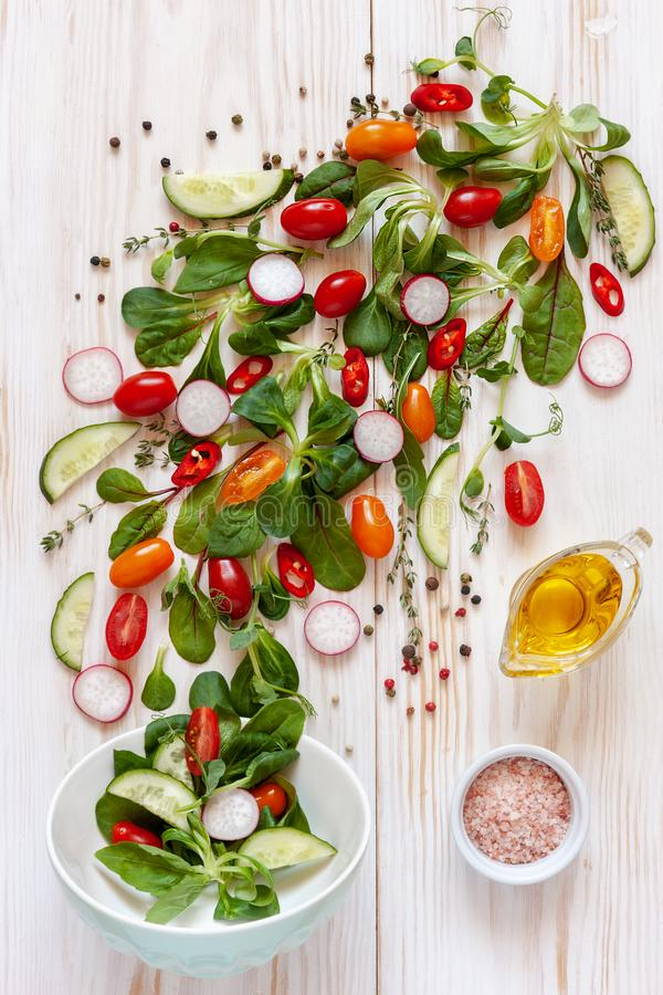 Verse ruwe tomaten, komkommers, babyspinazie en seizoengebonden greens Hoogste mening, close-up over witte houten achtergrond stock afbeelding