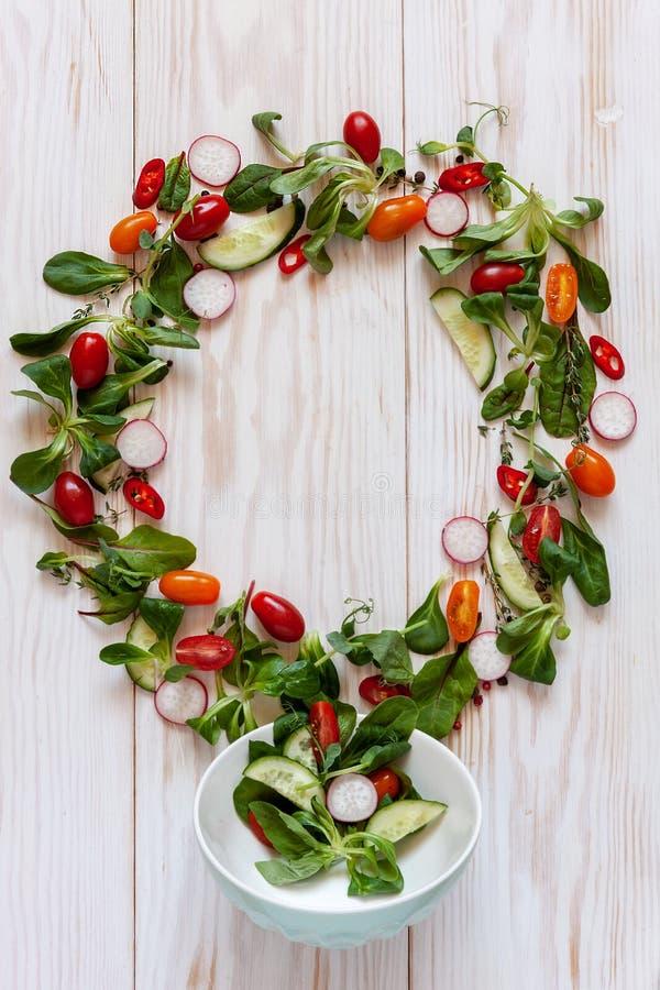 Verse ruwe tomaten, komkommers, babyspinazie en seizoengebonden greens Hoogste mening, close-up over witte houten achtergrond stock foto's