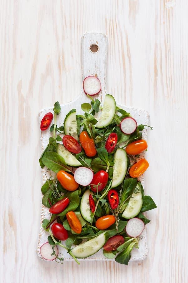 Verse ruwe tomaten, komkommers, babyspinazie en seizoengebonden greens Hoogste mening, close-up over witte houten achtergrond royalty-vrije stock fotografie