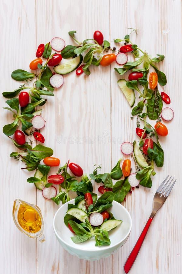 Verse ruwe tomaten, komkommers, babyspinazie en seizoengebonden greens Hoogste mening, close-up over witte houten achtergrond royalty-vrije stock afbeelding