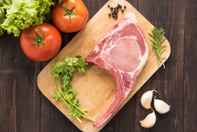 Verse Ruwe Varkenskoteletten en groente op houten achtergrond stock afbeeldingen
